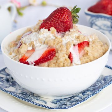 White bowl filled with oatmeal, topped with strawberries and cream.