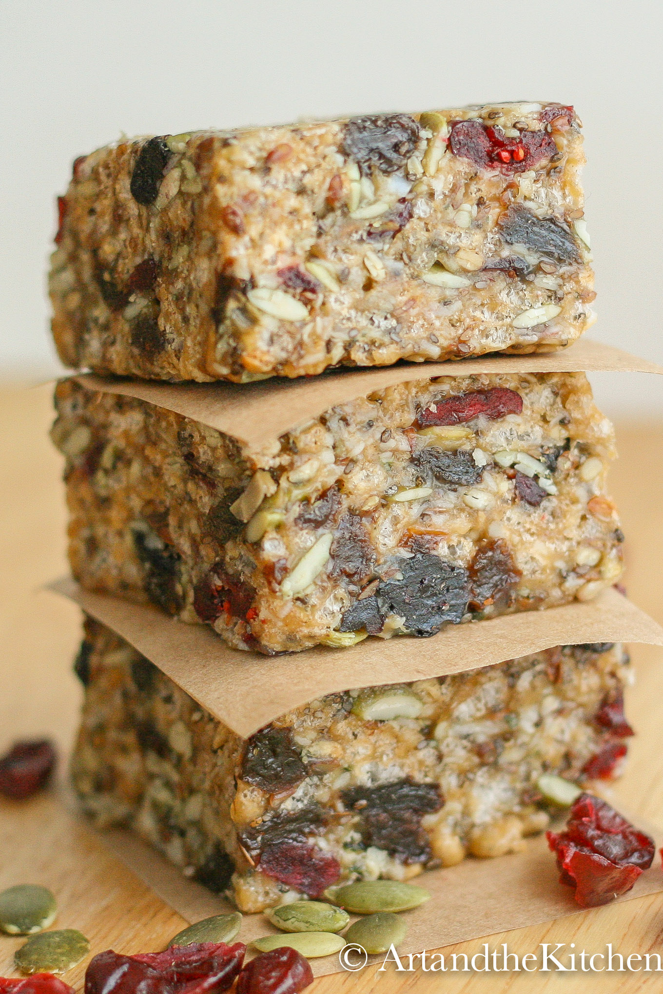 Stack of three homemade protein bars separated with brown parchment paper loaded with seeds and dry fruit.