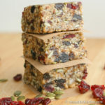 Stack of three homemade protein bars separated with brown parchment paper loaded with seeds and dry fruit