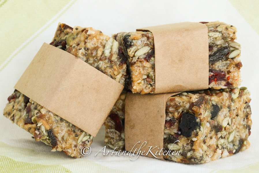Three homemade protein bars wrapped in brown parchment paper loaded with seeds and dry fruit