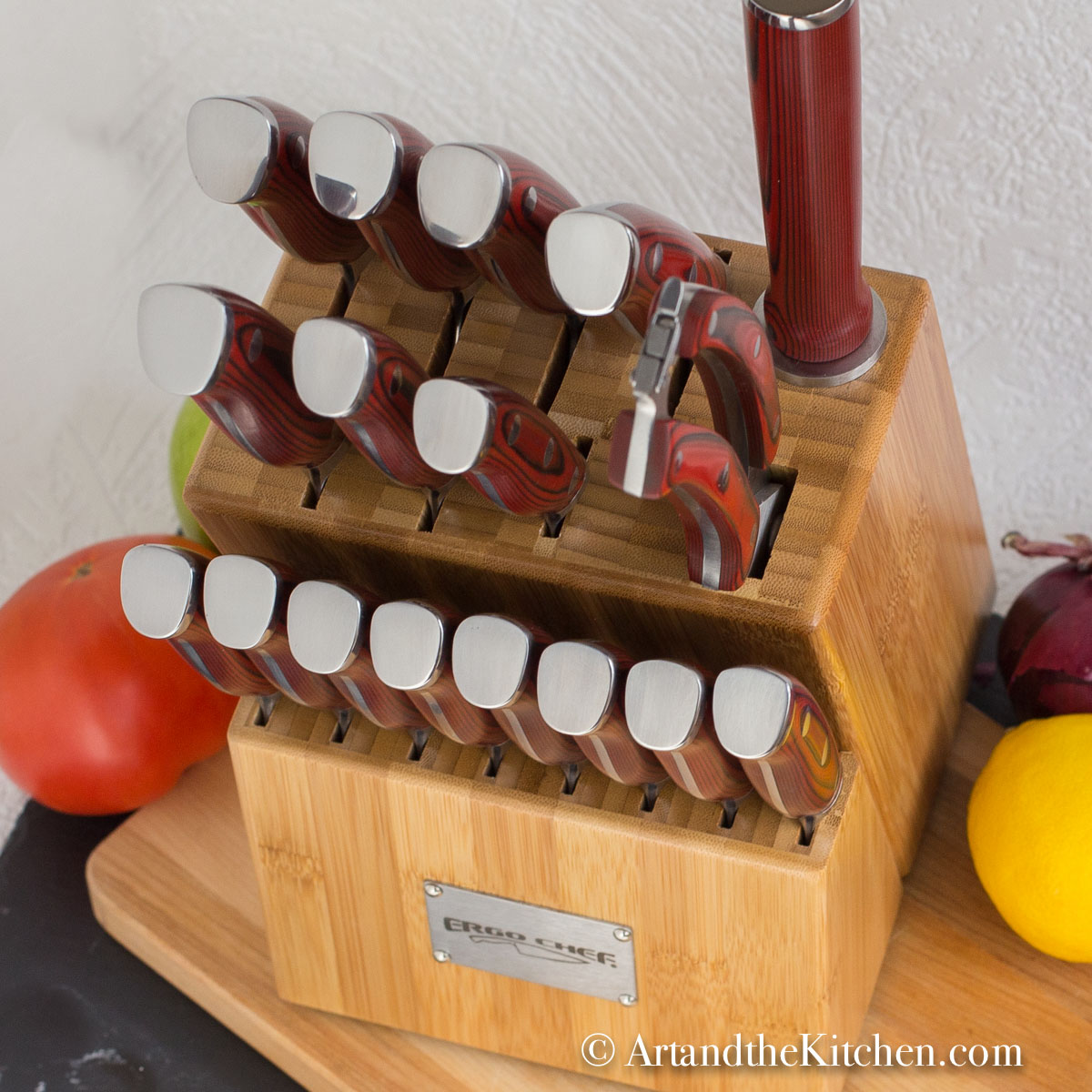 Wood knife block filled with set of knives on wood cutting board with fruit and vegetables in background.