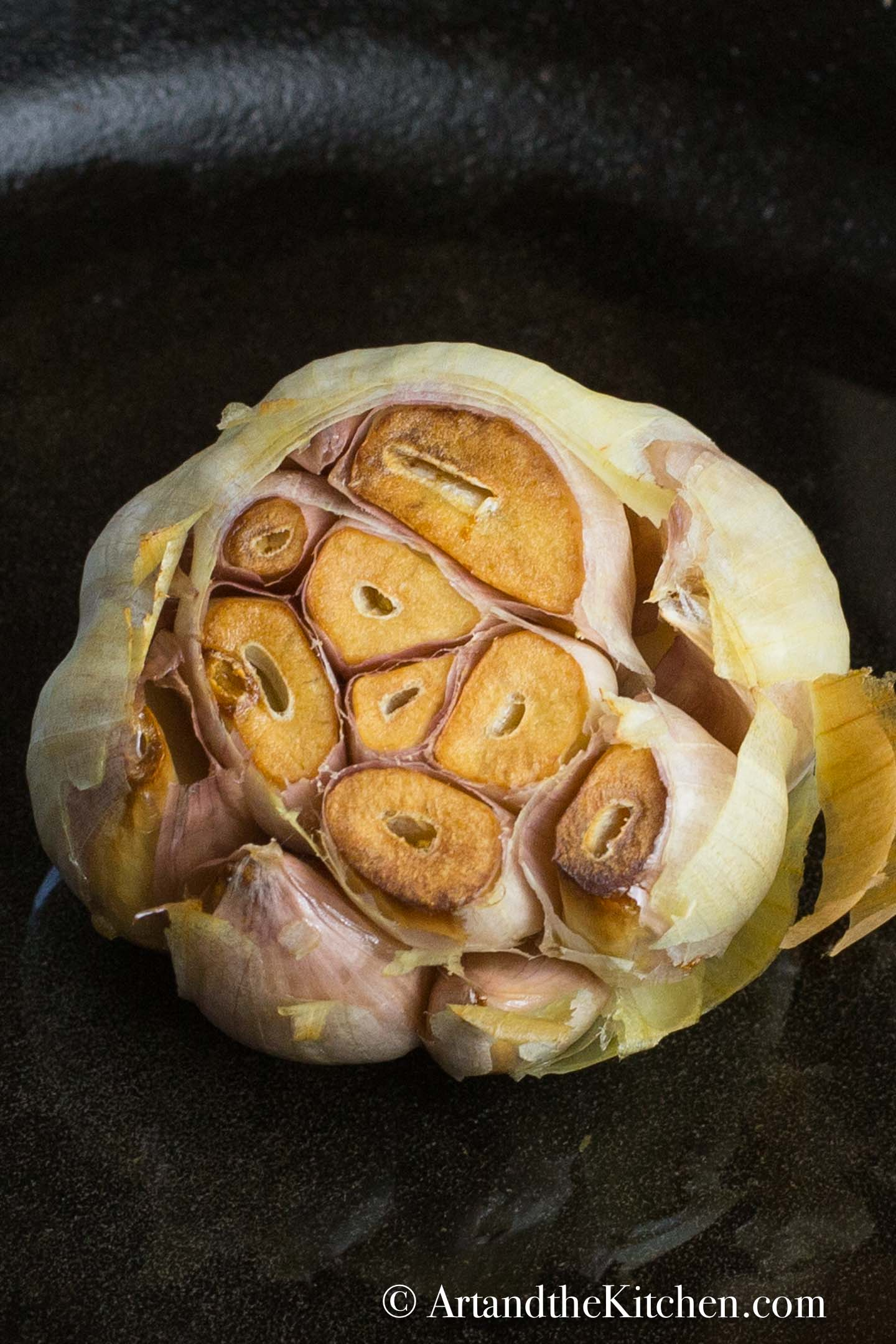 Head of garlic with the top sliced off roasted in a cast iron pan.