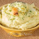 Yellow bowl filled with mashed potatoes, topped with clove of roasted garlic.