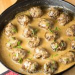 Meatballs simmering in a creamy sauce in a cast iron skillet, garnished with chives.