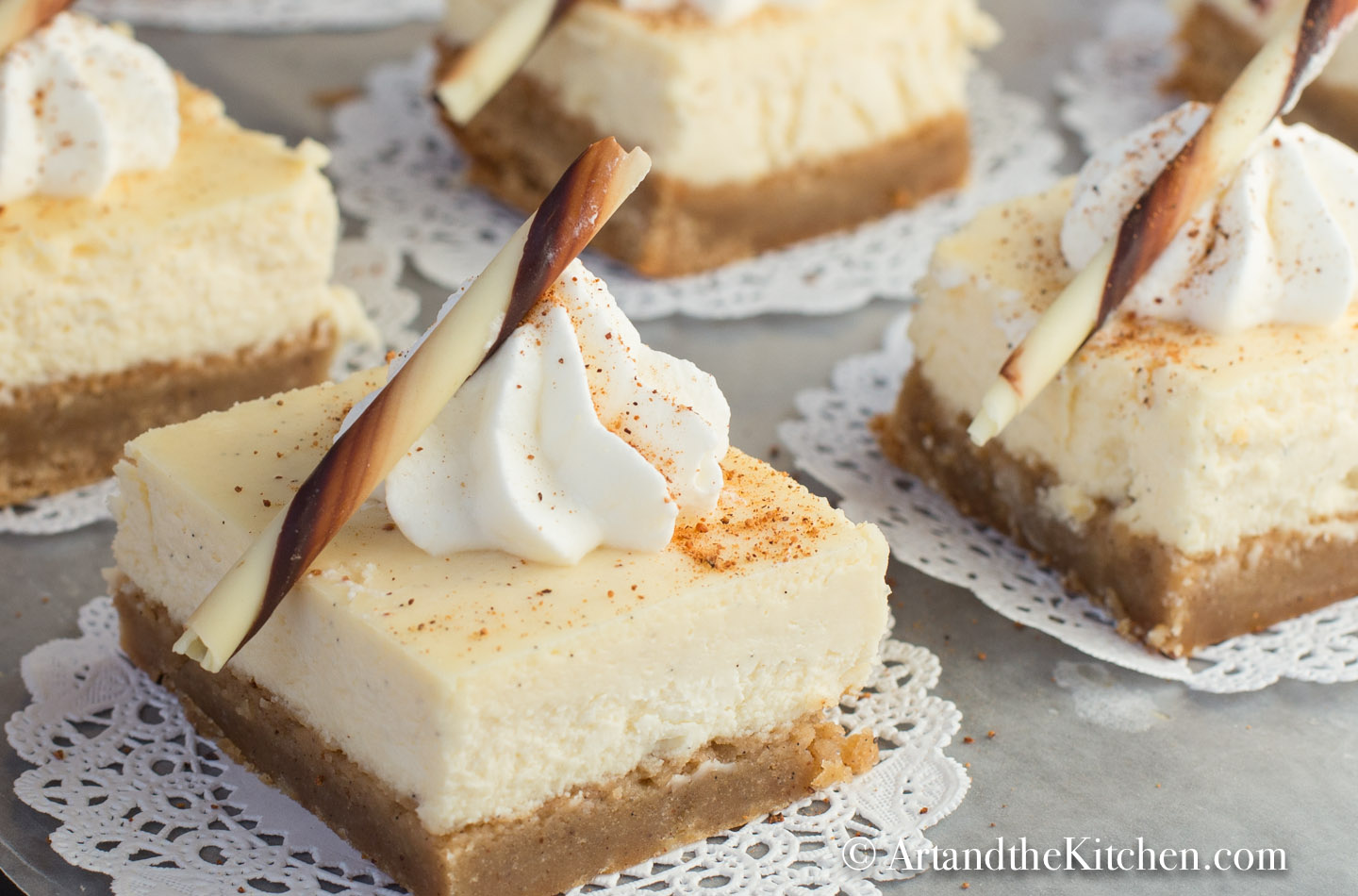Serving tray filled with cheesecake squares on paper dollies. Garnished with dollop of whipped cream and chocolate rod.