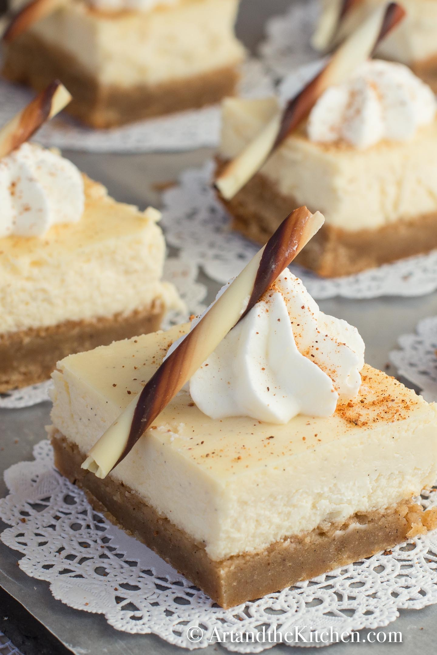 Squares of cheesecake on white paper dollies. Decorated with a dollop of whipped cream and chocolate stick.
