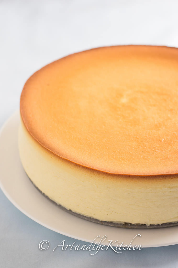 Whole cheesecake with golden baked top on white plate.