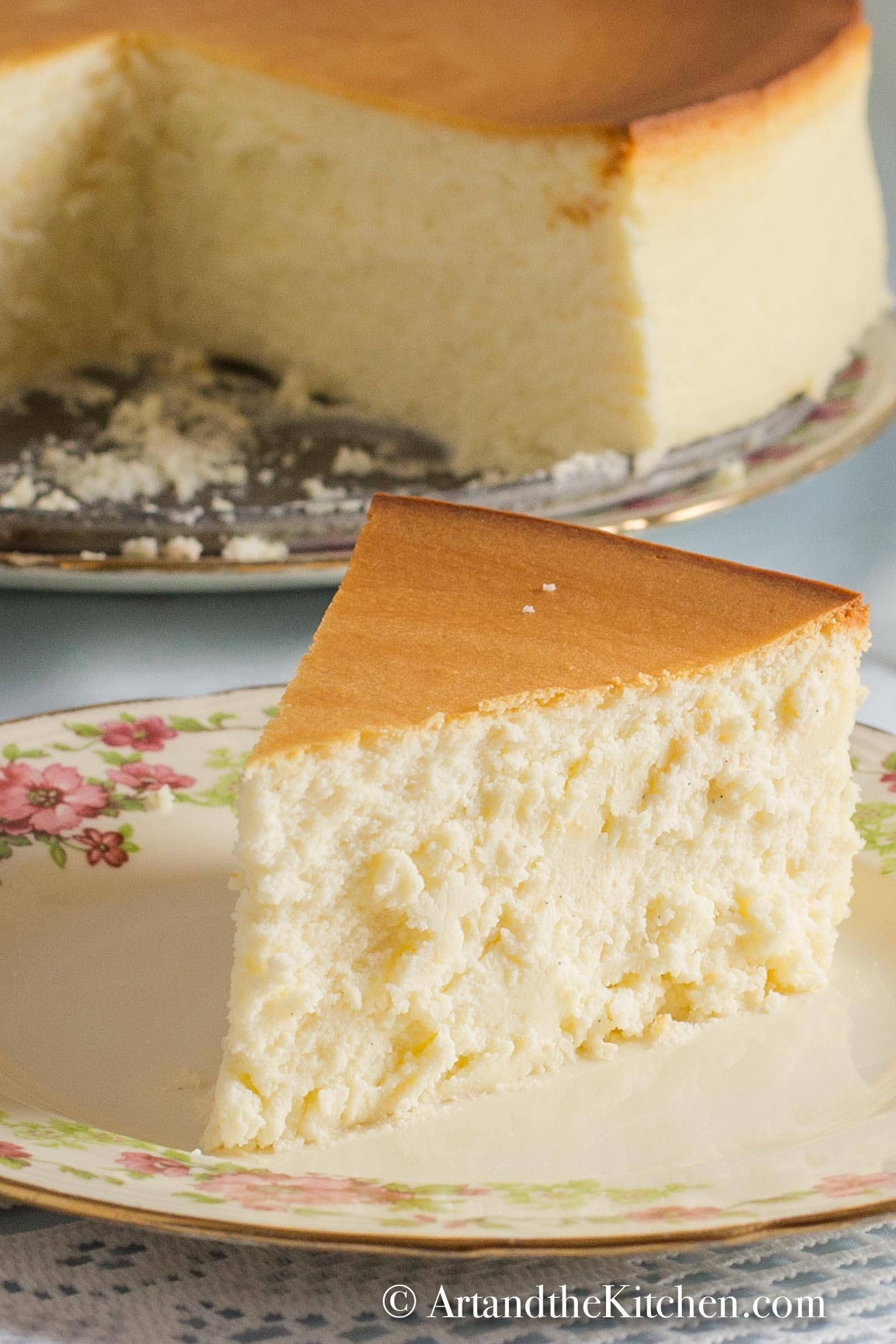 Slice of plain crustless cheesecake on decorative plate with whole cheesecake in background.