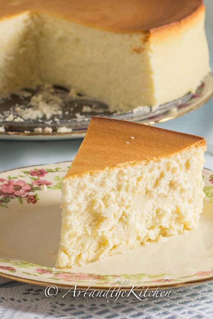 Slice of crustless, plain cheesecake on decorative plate, with whole cheesecake in background.