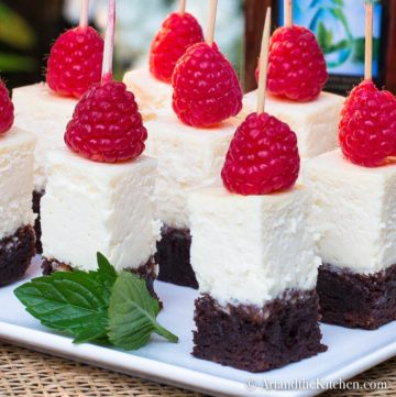 Bite size pieces of cheesecake with brownie crust topped with a raspberry held with wood toothpick