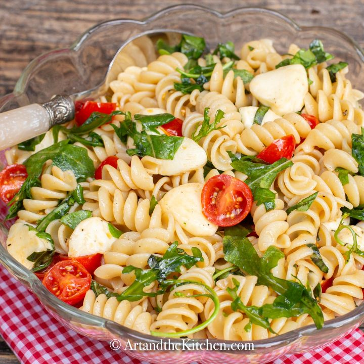 Rotini pasta tossed together with bocconcini, cherry tomatoes, arugula, and fresh basil.