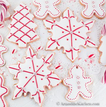 Sugar cookies cut into snowflake and gingerbread men shapes, coated with white royal icing and decorated with red dots and lines.