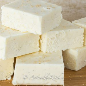 Stack of squares of white fudge made with eggnog flavor.