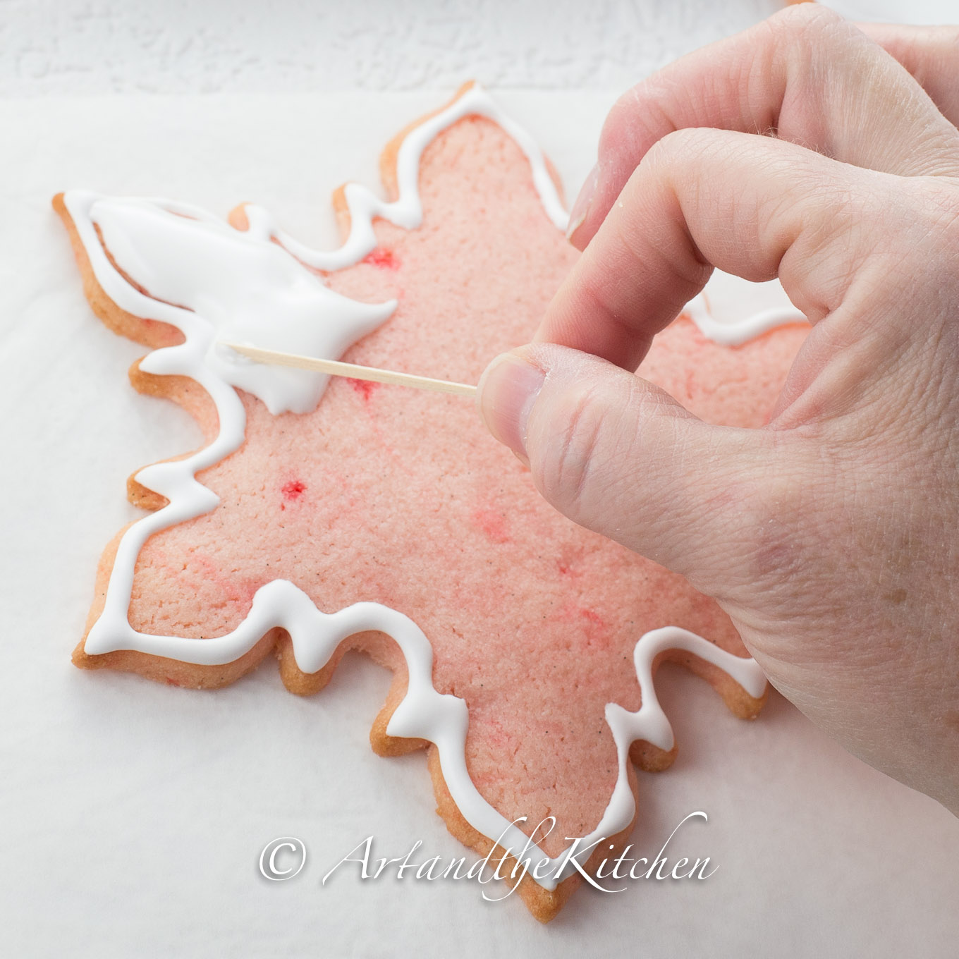 Pink snowflake cookie being decorated with royal icing.
