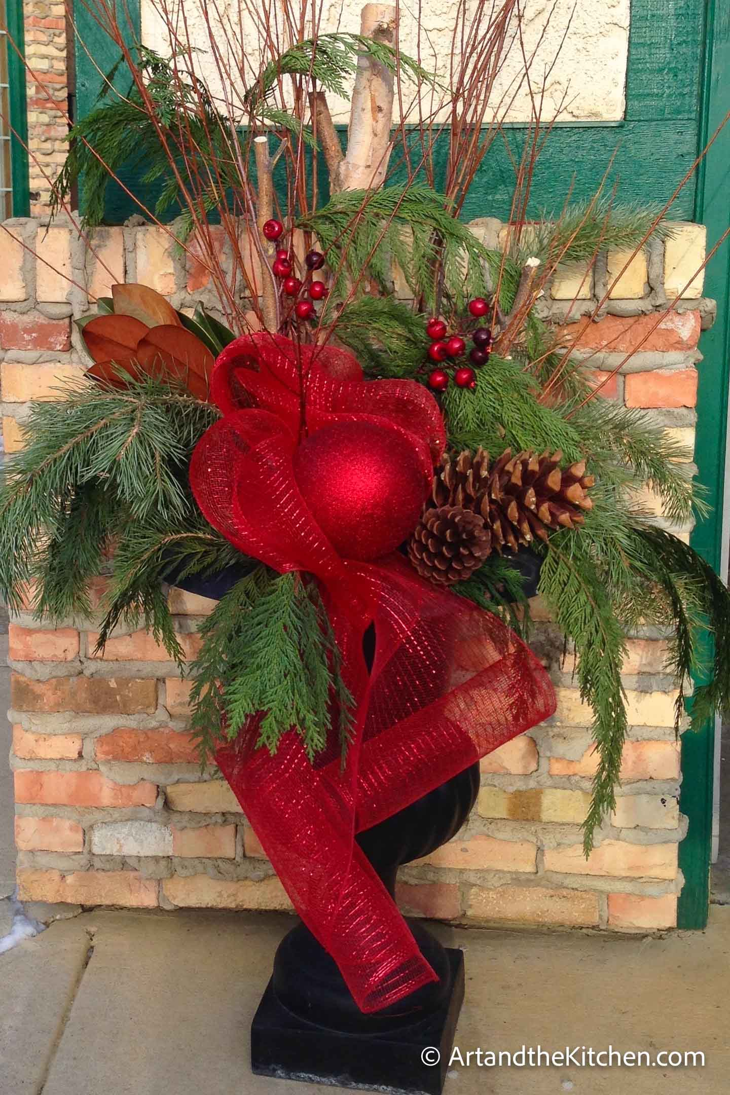 Outdoor Christmas planter with greenery, tree branches and decorations.