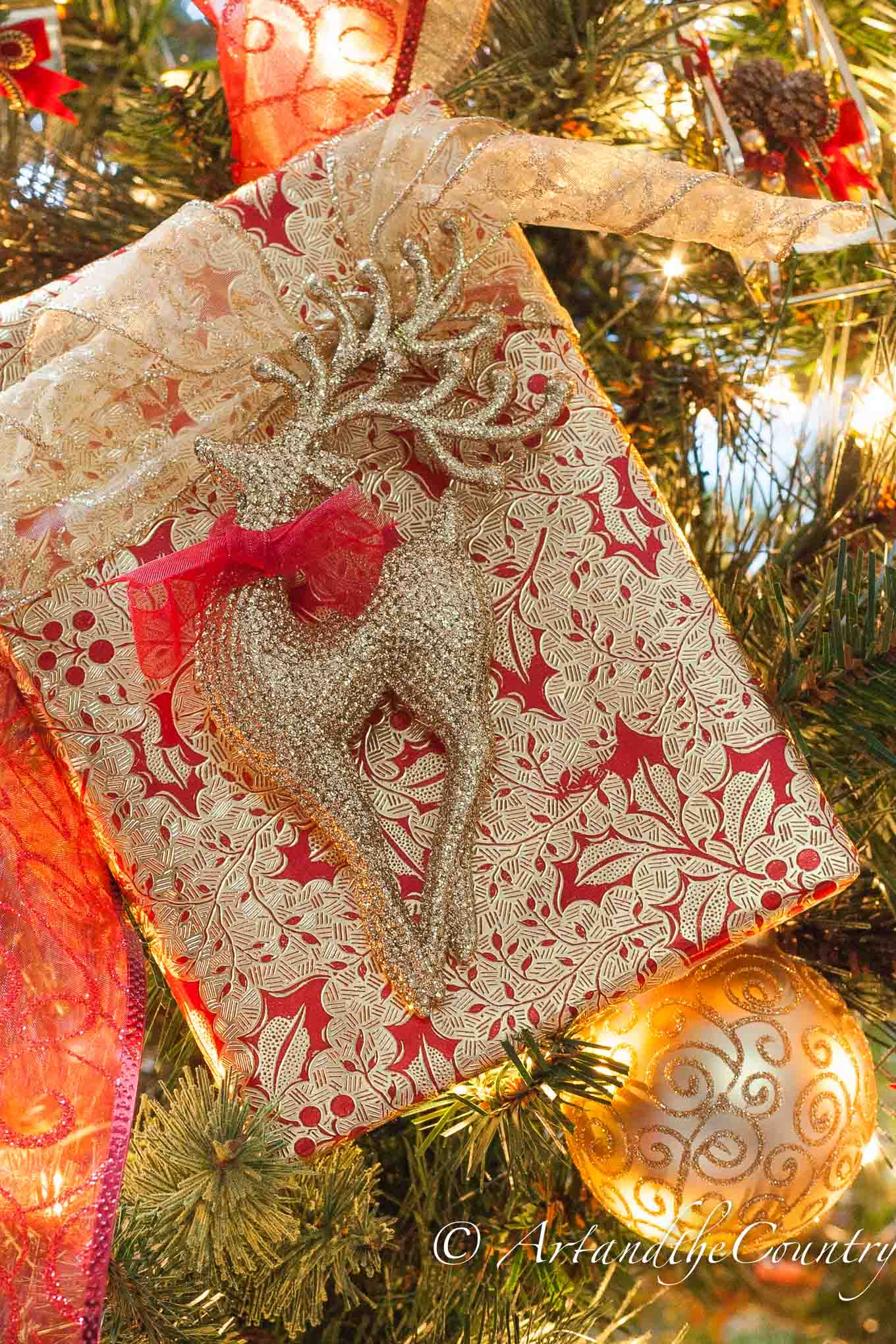 Christmas gift wrapped in red and gold paper and ribbon with gold reindeer ornament.