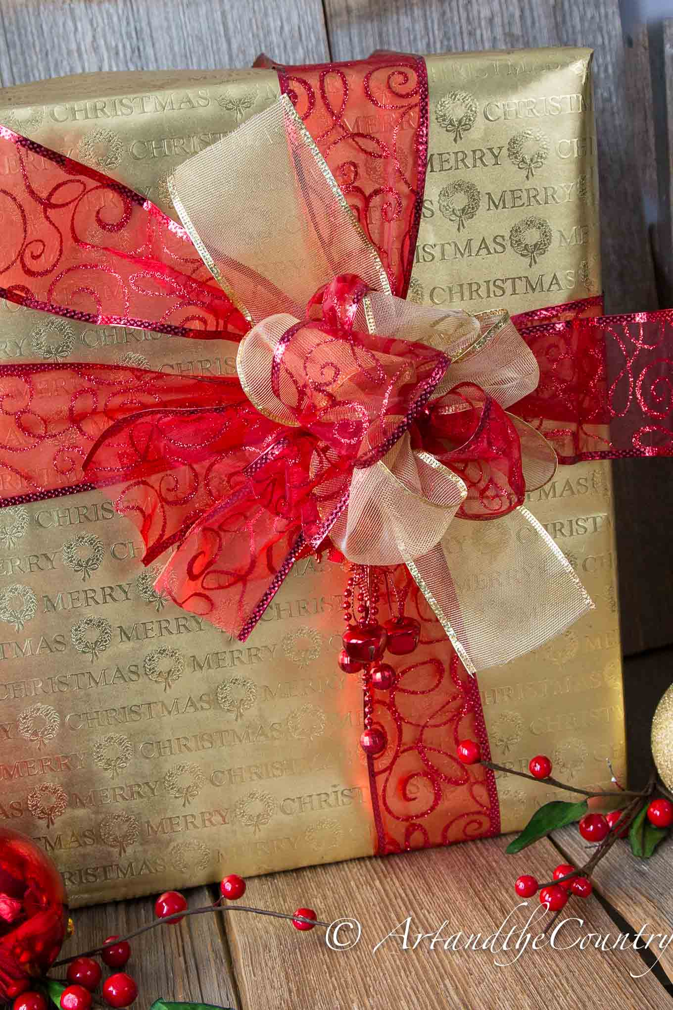 Christmas gift wrapped in gold paper with red and gold ribbon.