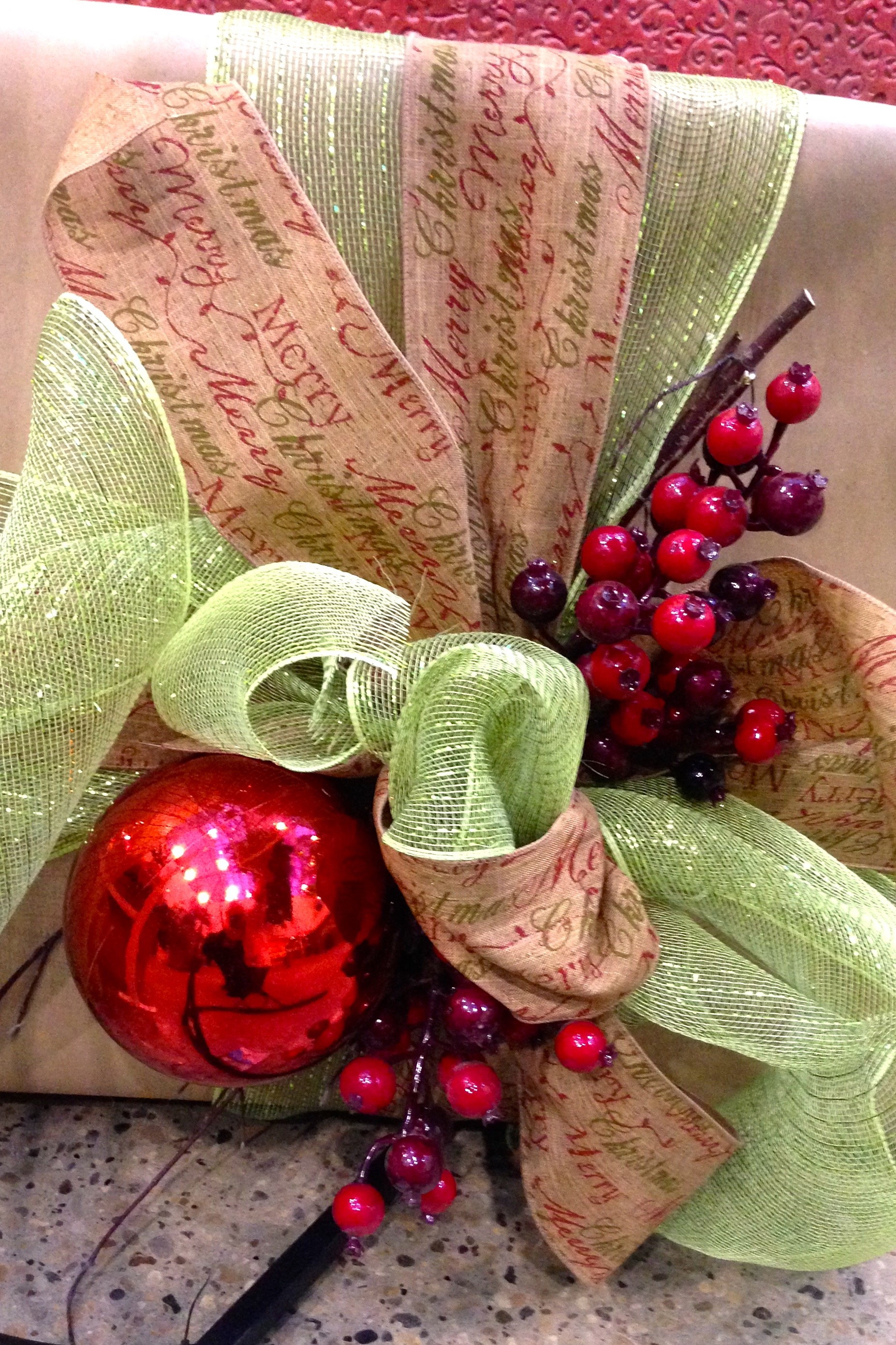 Christmas gift wrapped in brown paper and green and burlap bows with red ornaments.