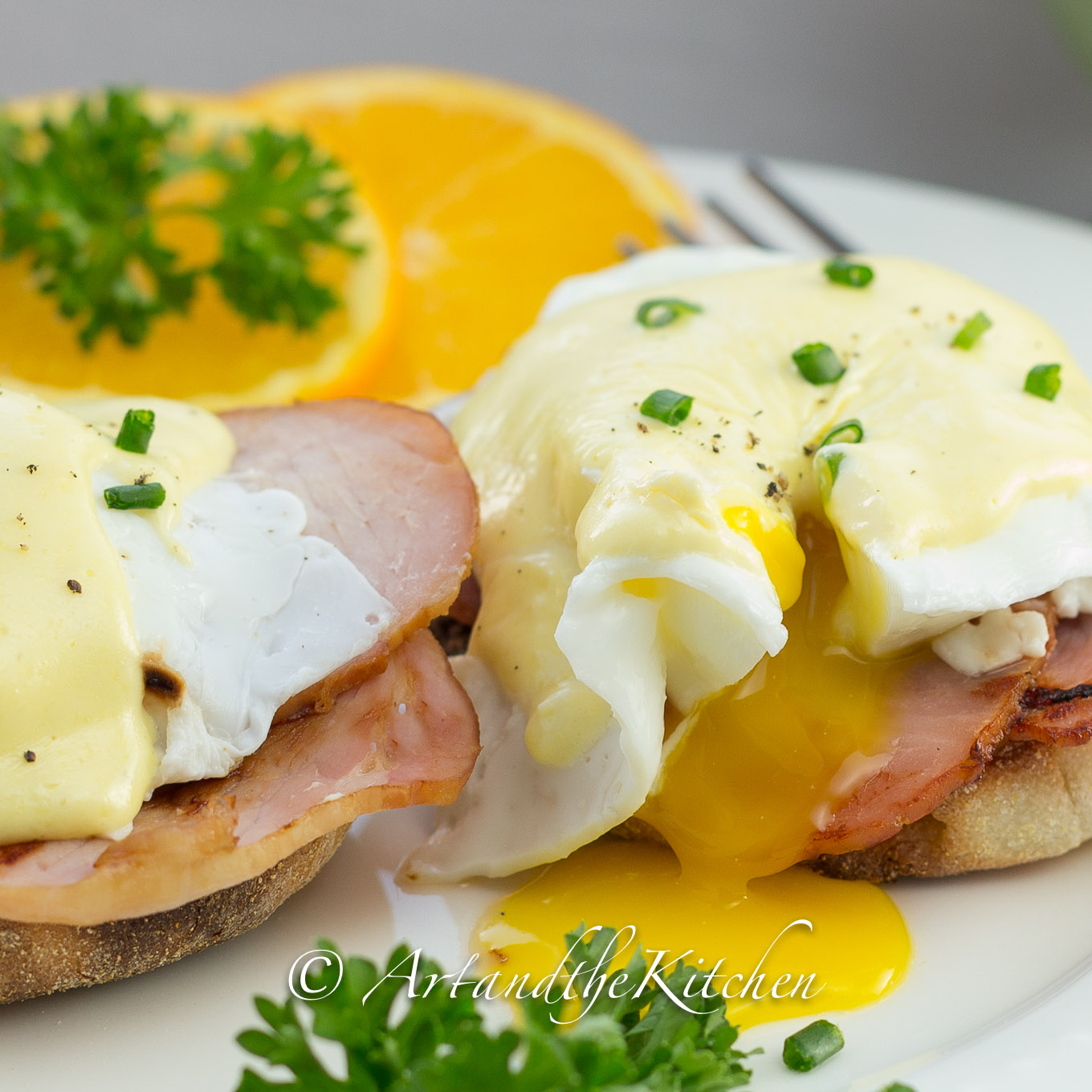 Eggs Benedict with ham, garnished with orange slices and parsley.
