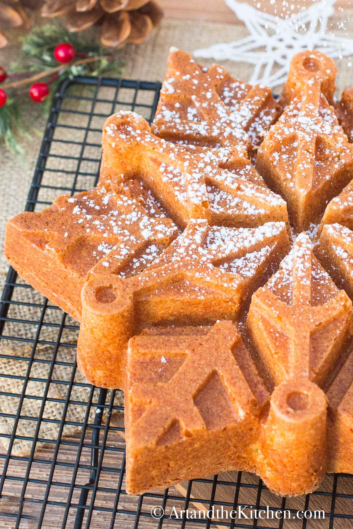 Snowflake shaped bundt cake made with eggnog, sprinkled with confectioners sugar.