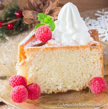 Slice of bundt cake made with eggnog, topped with whipped cream and fresh raspberries.
