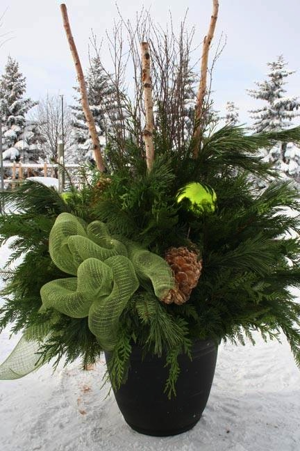 Outdoor Christmas planter with greenery , green bow and pinecones.