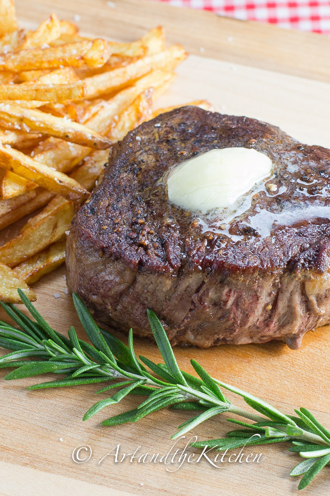 Cooked steak with pat of butter on top, with french fries and a sprig of rosemary.