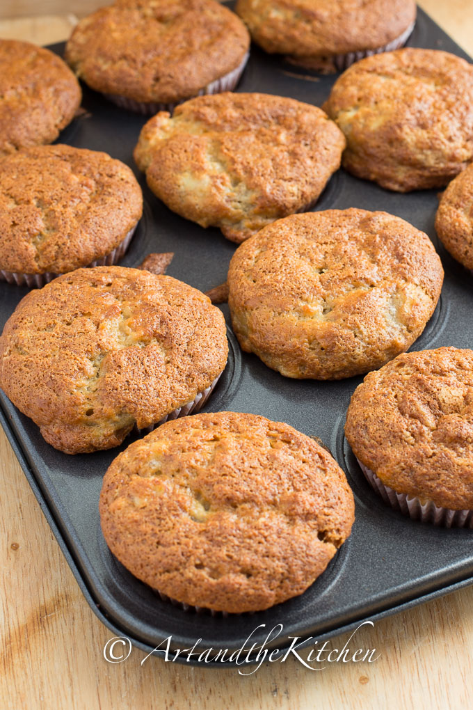 Muffin tin full of banana muffins with golden brown crisp tops.
