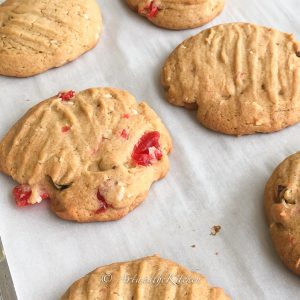 Baking sheet filled with baked cookies that have maraschino cherries, walnuts and coconut in them.