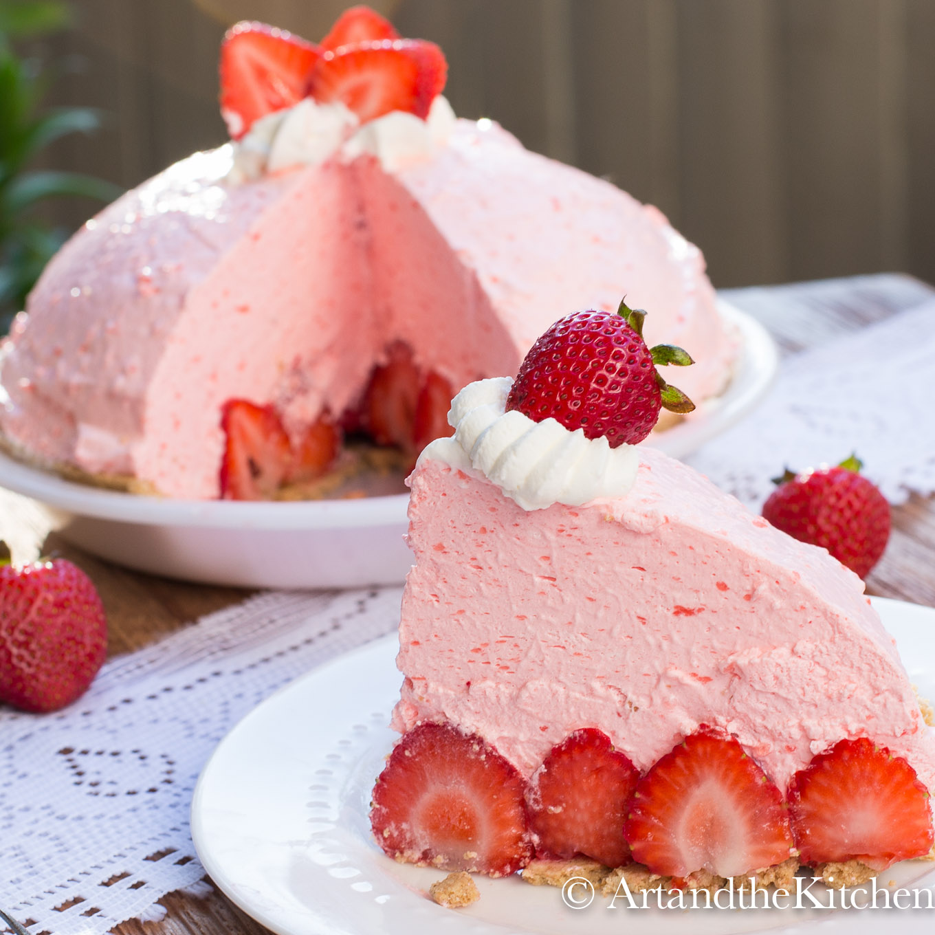 Slice of tall no-bake strawberry pie with fresh strawberries with whole pie in background.