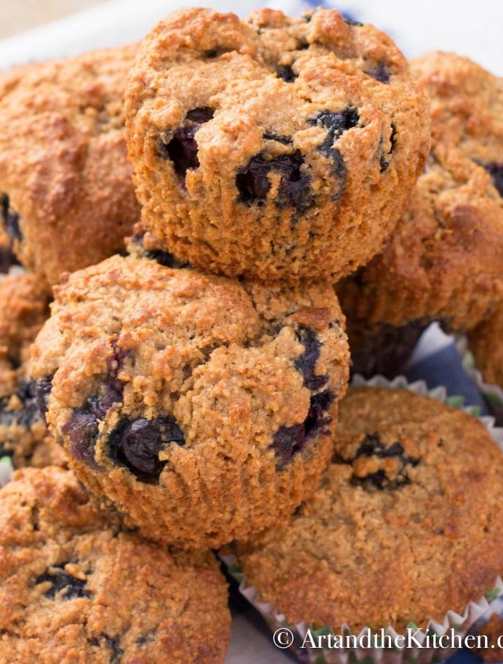 Bran muffins that are loaded with fresh blueberries on a blue gingham tablecloth.