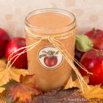 Glass jar with apple label on it, filled with applesauce. Jar has straw ribbon tied around it.
