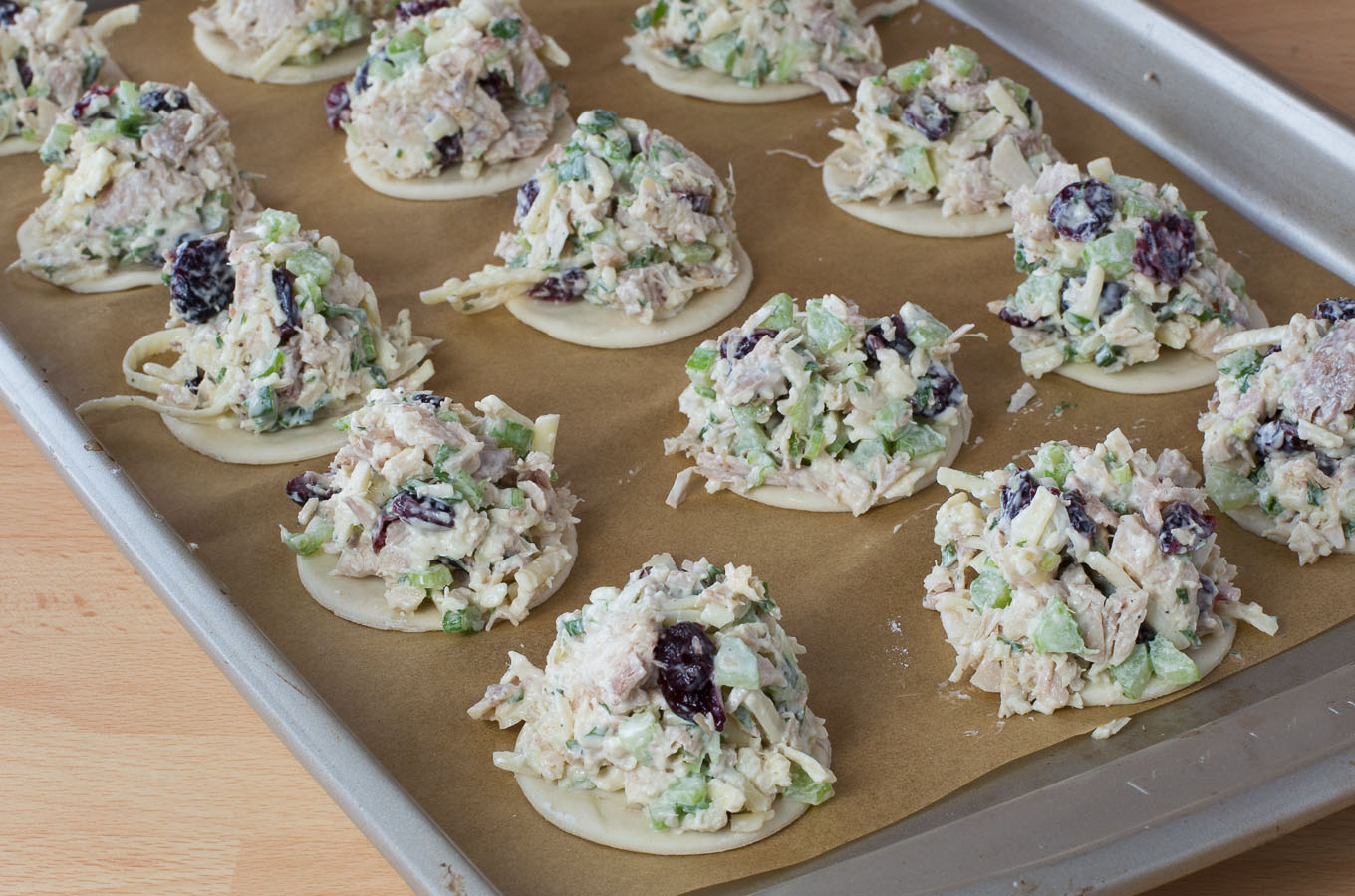 Bites of puffed pastry topped with turkey salad mix and cranberries.