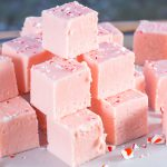 Stack of pink fudge made with ground up candy canes.