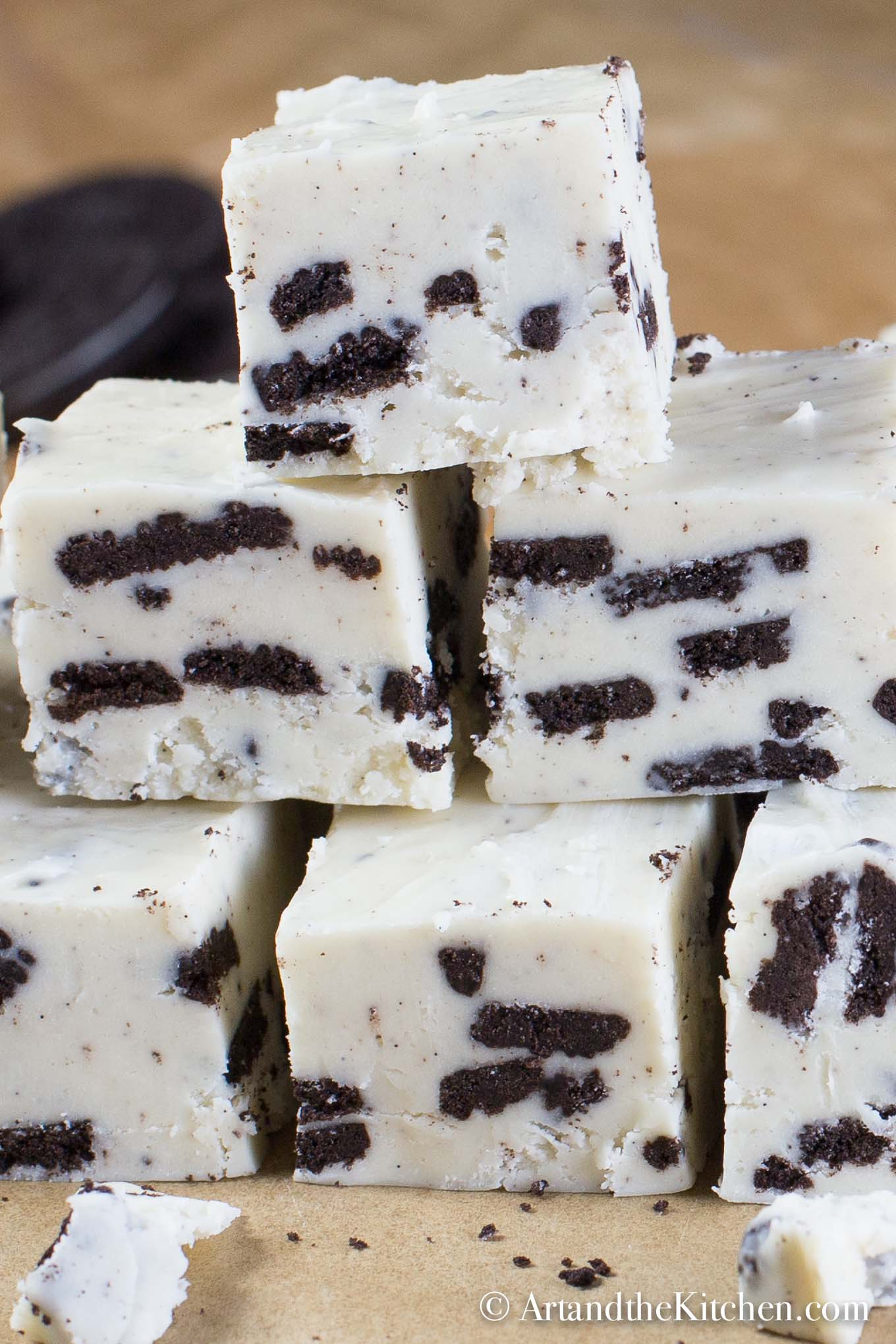 Stacked cubes of fudge made with white chocolate and Oreo cookie pieces.