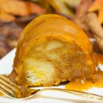 Slice of pumpkin flavored bread pudding covered with caramel sauce. Served on a white plate with gold fork.