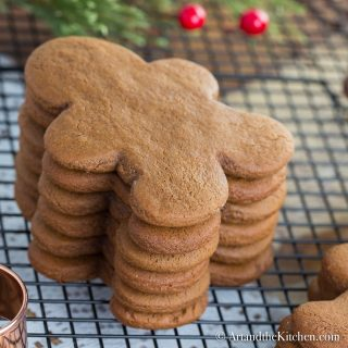 Stack of gingerbread men cookies on cooling rack with copper cookie cutter.