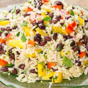 Colorful salad with coconut rice, black bean, pineapple, red peppers, onion, and cilantro on a green plate.