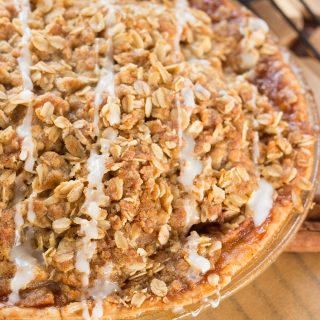 Apple pie in a glass pie plate with a crunchy oatmeal top, drizzled with icing.