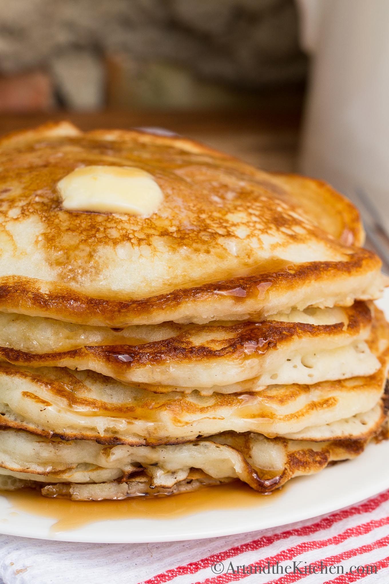 stack of pancakes with dollop of butter and syrup on top