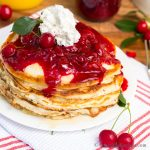 Pancakes stacked and topped with cherry sauce and whipped cream