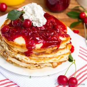 thick pancake stack topped with cherry sauce and whipped cream