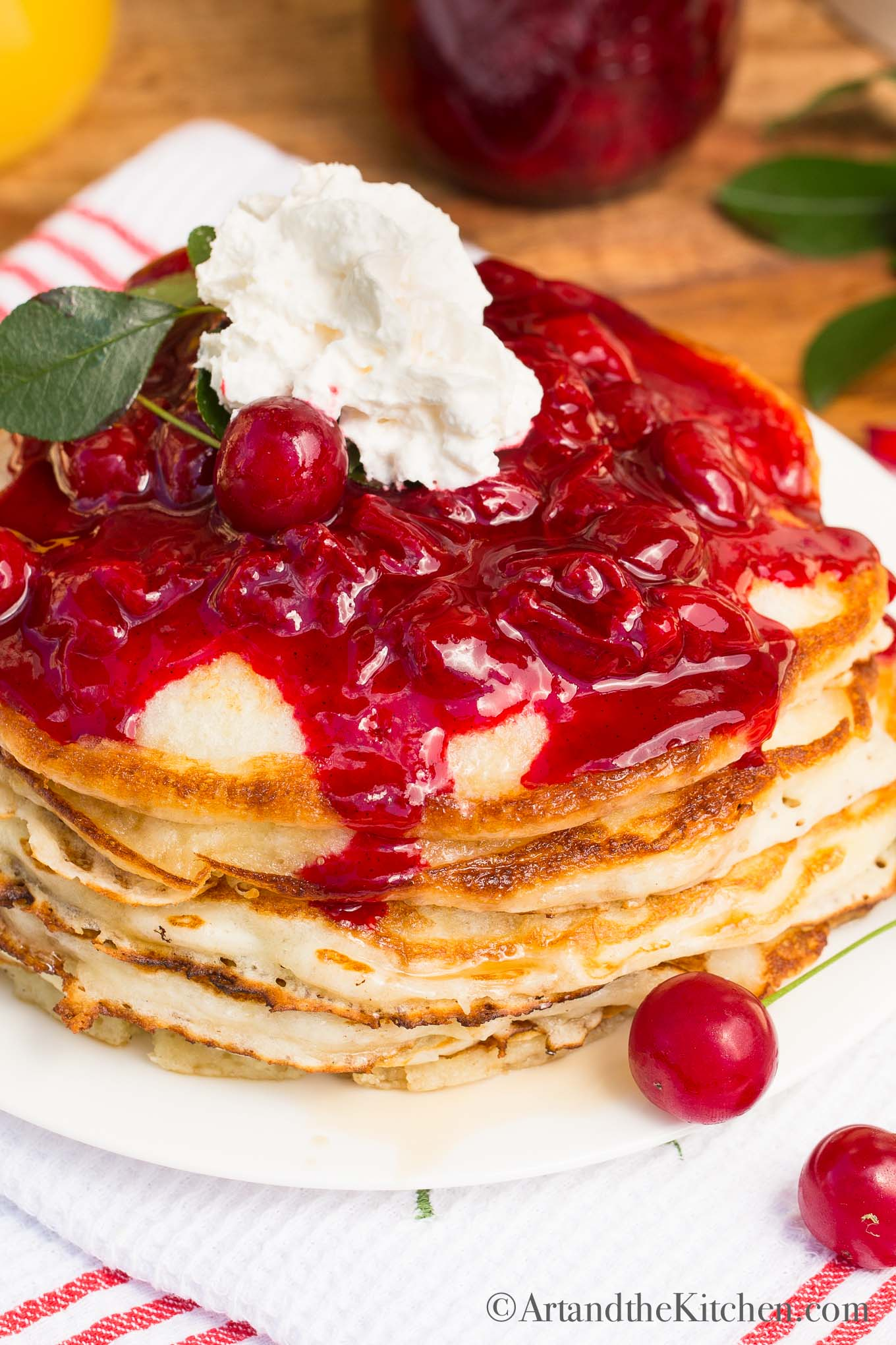 stack of fluffy pancakes topped with cherry sauce and whipped cream