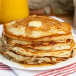 Stack of golden brown pancakes topped with a pat of butter and maple syrup.