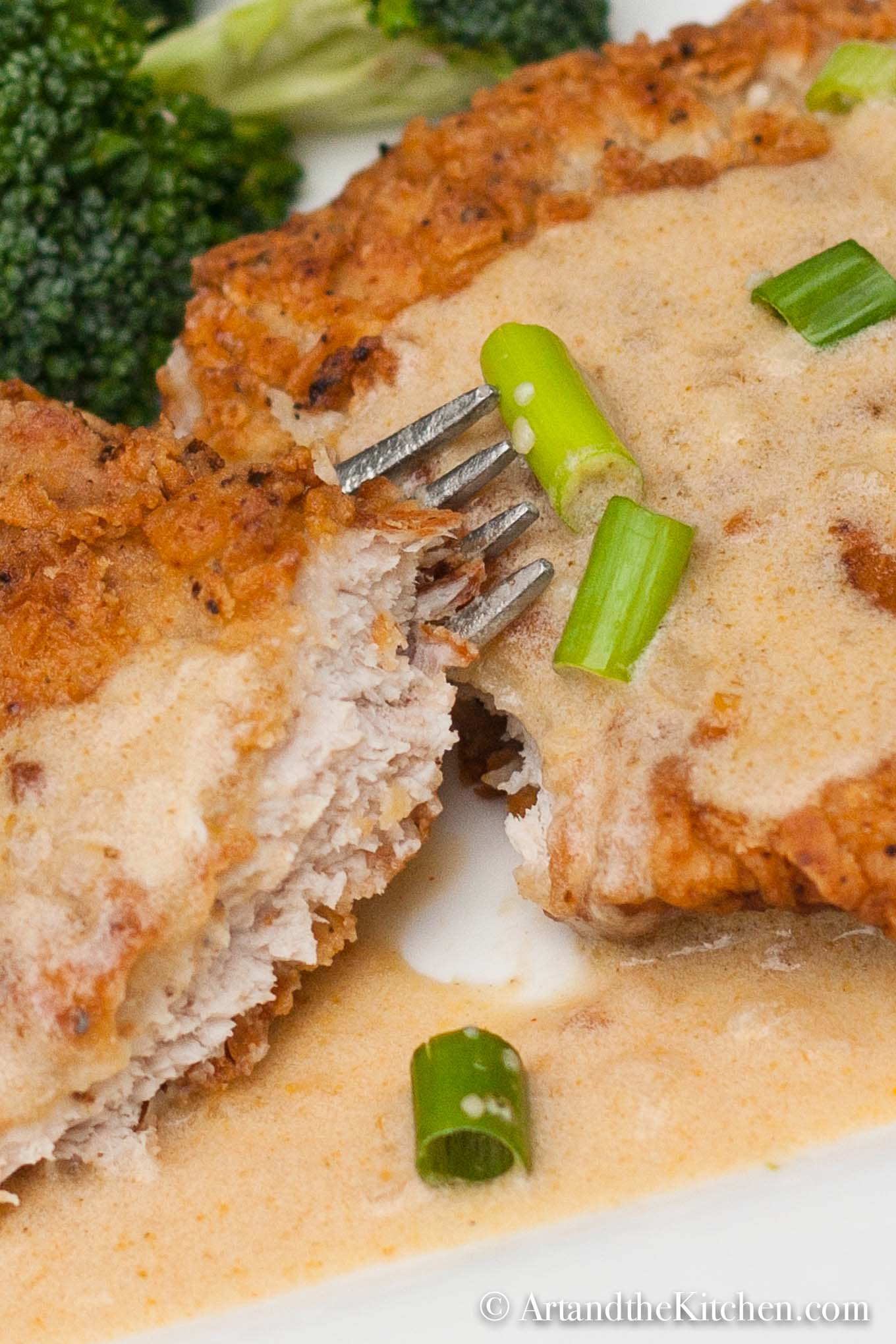 Golden brown fried pork schnitzel topped with a mustard sauce and garnished with green onion slices.