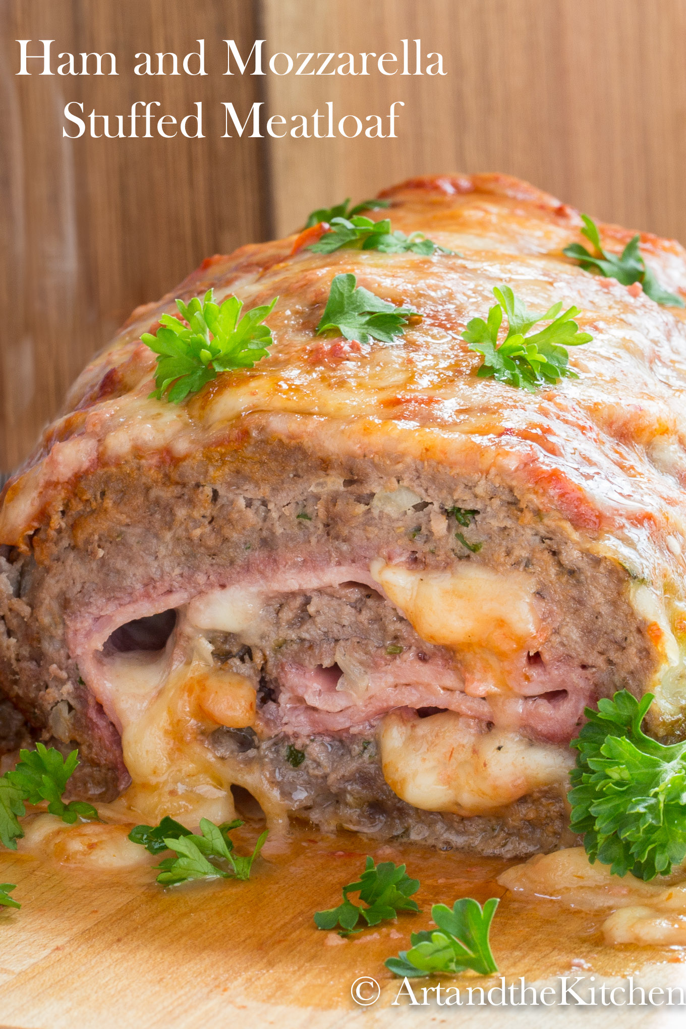 Meatloaf stuffed with ham and mozzarella cheese, garnished with parsley leaves.