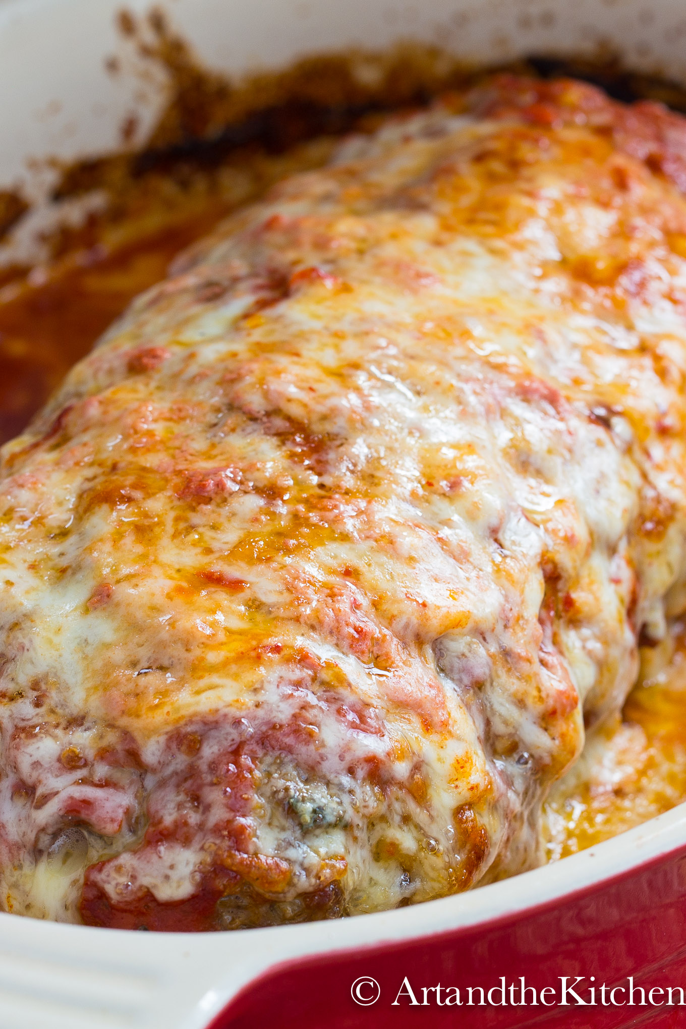 Meatloaf in baking dish covered with melted mozzarella cheese.