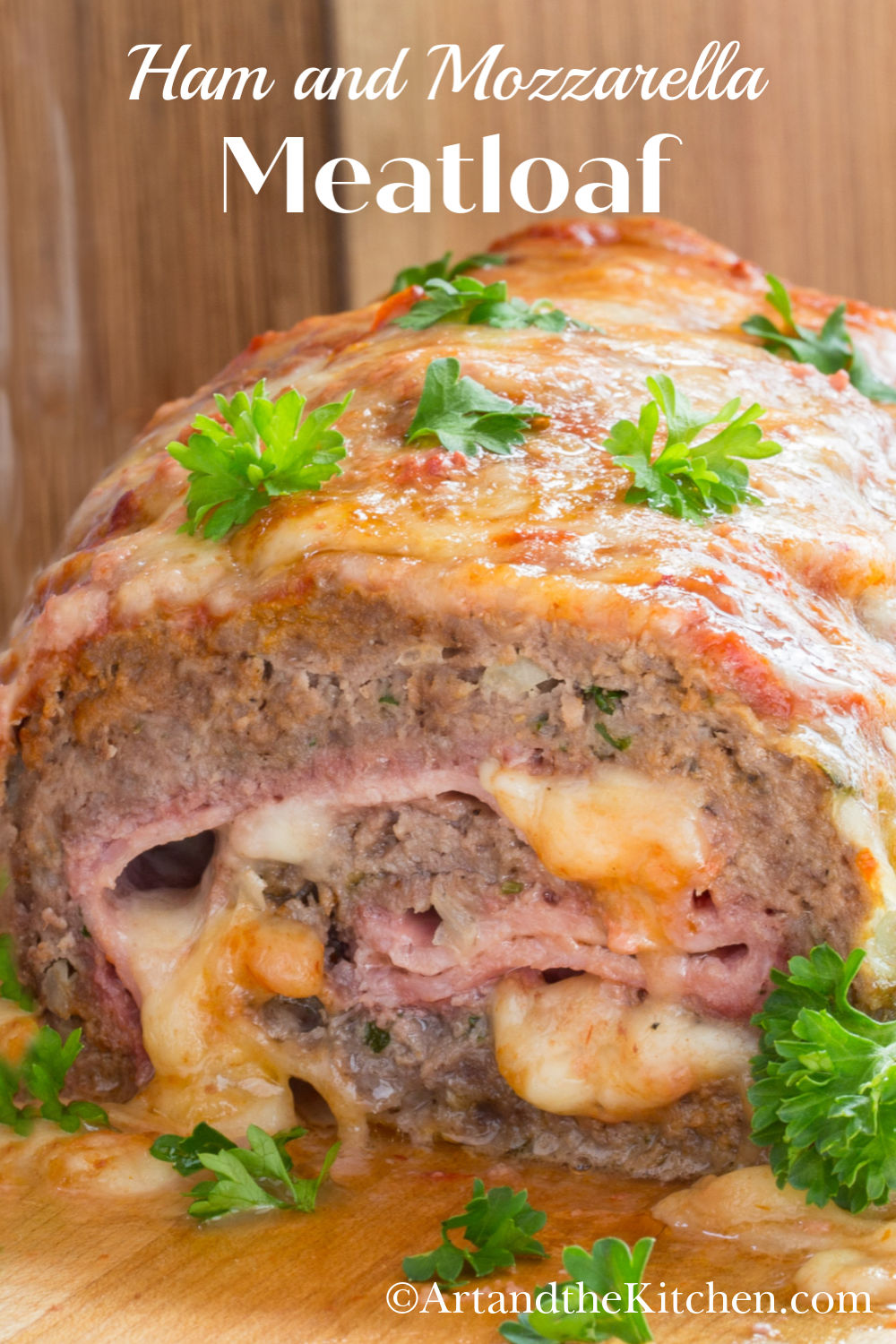 Homemade meatloaf stuffed with slices of ham and mozzarella cheese. This easy to make recipe takes meatloaf to a whole new level of delicious! Ground beef is mixed with bread crumbs and an assortment of spices, then rolled in a layer of ham and cheese. Topping off the meatloaf is rich tomato sauce and melted cheese.  via @artandthekitch