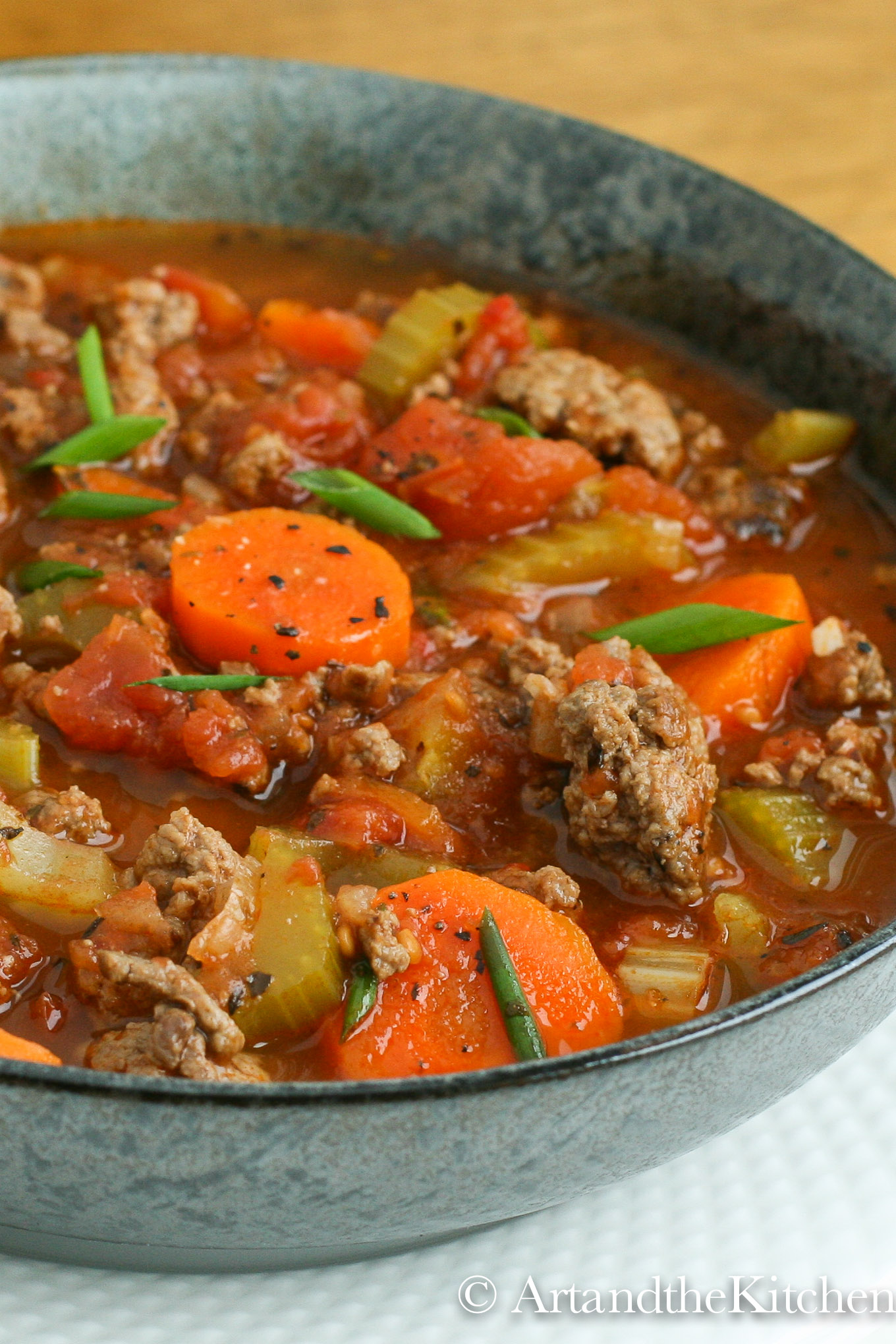 Green bowl filled with soup made with chunks of ground beef, carrots, tomatoes and celery.