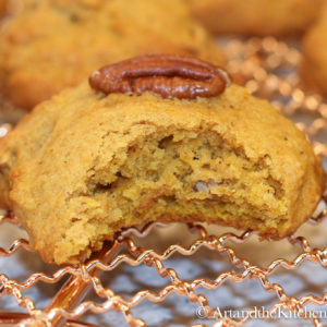 Pumpkin cookie with bite out of it on copper wire rack.
